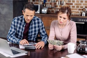 Man and woman reviewing money with cash and calculater